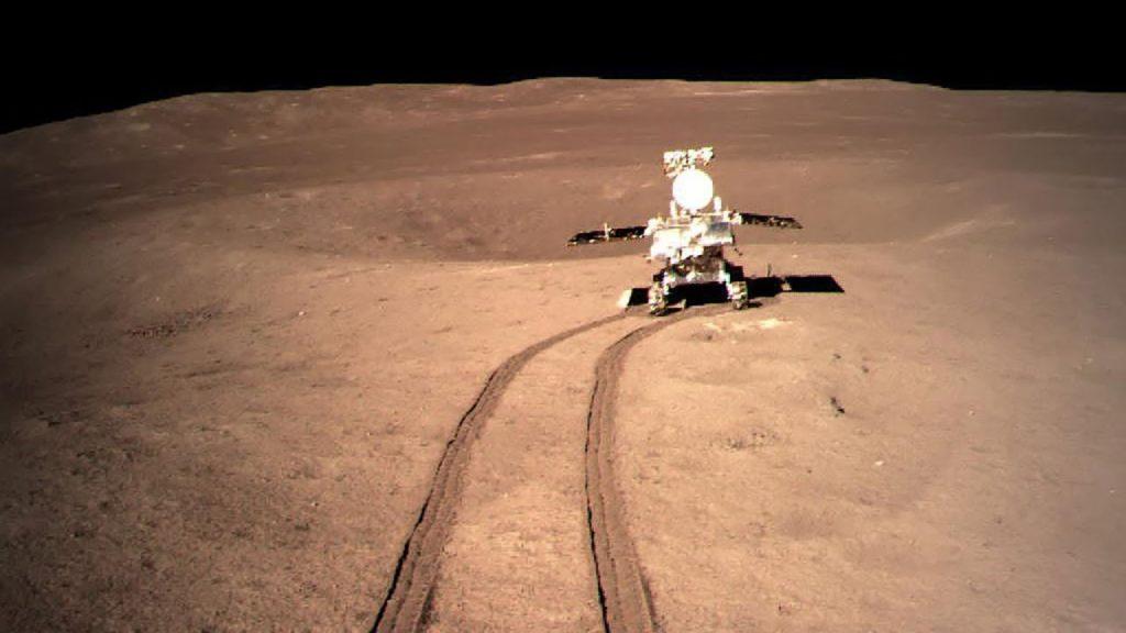Le rover Yutu-2 à la surface de la Lune. On le voit au bout d'un chemin tracé par ses roues dans le sol lunaire, de couleur rosé.