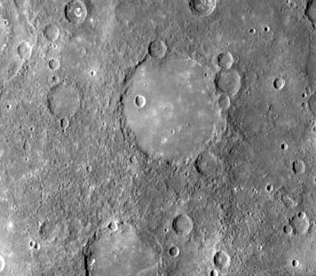 Photo en couleurs grises d'une zone de la surface de Mercure où l'on voit un grand cercle régulier, une plaine lisse, qui illustre un volcanisme passé.