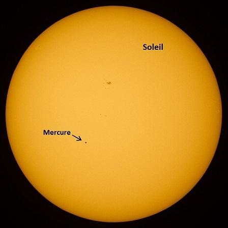 Le Soleil est vu en entier, orange clair sur fond noir, et un petit point noir représente Mercure qui passe devant notre étoile lors de son transit en mai 2016.