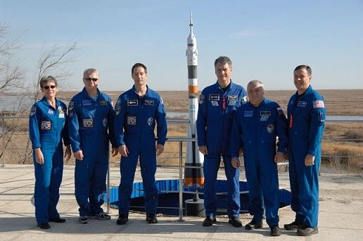 Photo sur la base de Baïkonour au soleil de l'équipage de l'expédition 50-51 vers l'ISS. Trois astronautes principaux à gauche et trois remplaçants à droite, tous en combinaisons bleues.