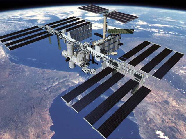 Vue globale de l'ISS avec la Terre en arrière plan et en orbite la station, notamment ses 24 panneaux solaires bien en évidence.