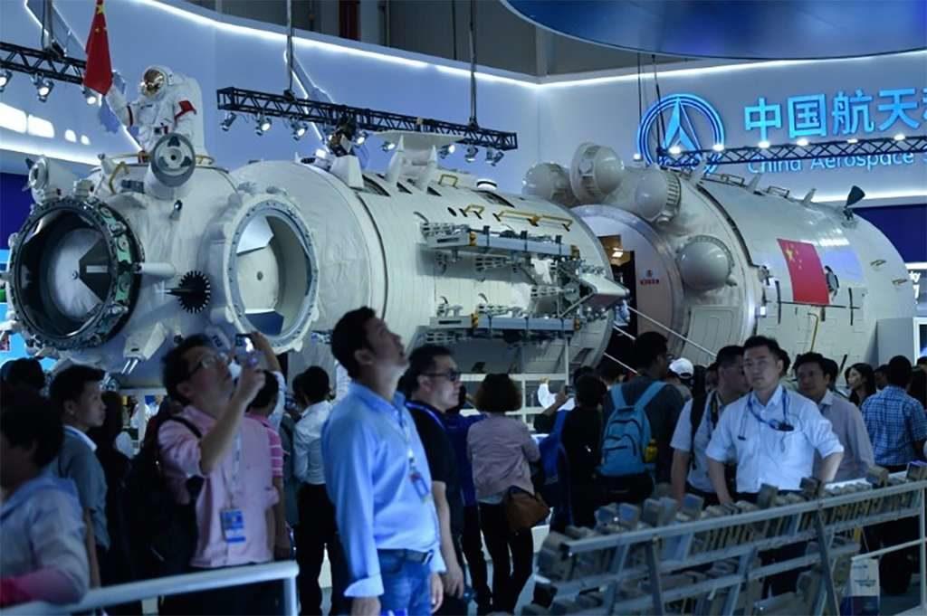 Maquette taille réelle de la future station orbitale chinoise : on la voit lors de sa présentation officielle, entourée d'une foule de Chinois, à l'intérieur d'un bâtiment.