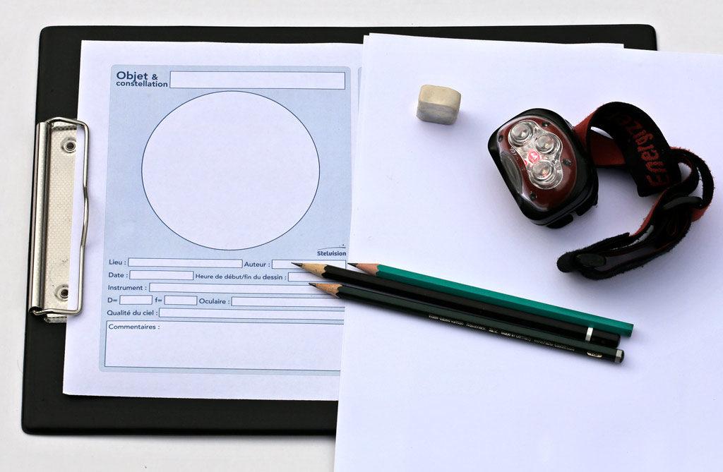 Photo avec une planchette munie d'une pince, un gabarit et une feuille blanche, quelques crayons graphite, une gomme et une lampe rouge qui sont les principaux accessoires pour débuter le dessin astronomique.