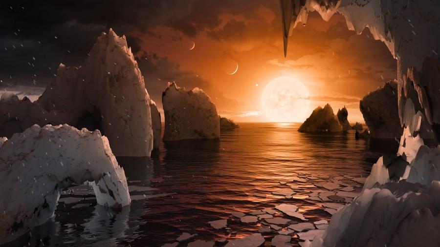 Vue d'artiste pour nous permettre d'imaginer à quoi pourrait ressembler la surface de l'exoplanète TRAPPIST-1f: au-dessus d'un océan, on voit l'étoile qui apparaît grosse car elle est très proche, et rouge car elle est peu chaude. D'autres planètes voisines sont visibles dans le ciel ! image NASA