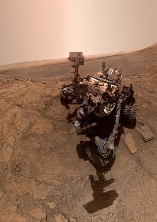 Selfie pris du rover Curiosity par lui-même en octobre 2019 : on y voit le rover sur le sol martien de jour, son ombre sur le sol vers l'avant de la photo.