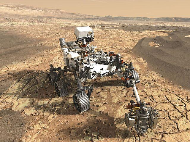 Vue d'artiste du rover de Mars 2020 sur le sol martien. Il ressemble beaucoup à Curiosity actuellement sur Mars avec ses six roues, son mât où se trouve SuperCam et son bras mécanique.