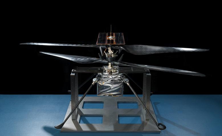 Photo du modèle de vol du Mars Helicopter Scout, l'hélicoptère qui va embarquer sur Mars 2020. Il est posé sur un socle bleu, au centre de l'image, on voit bien ses 4 pales.