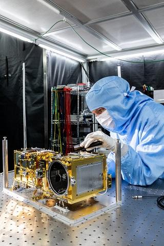 Un ingénieur en train de travailler en blouse bleue sur le modèle de vol de SuperCam : instrument doré au premier plan.