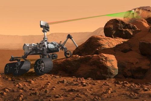 Vue d'artiste de SuperCam en action : on voit l'instrument en haut du mât qui tire au laser vert sur les roches.