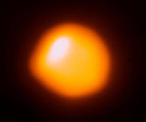 Bételgeuse vue par le télescope Alma : sur fond noir, on voir une sphère rouge-orangé irrégulière dotée d'une zone plus brillante en haut à gauche.