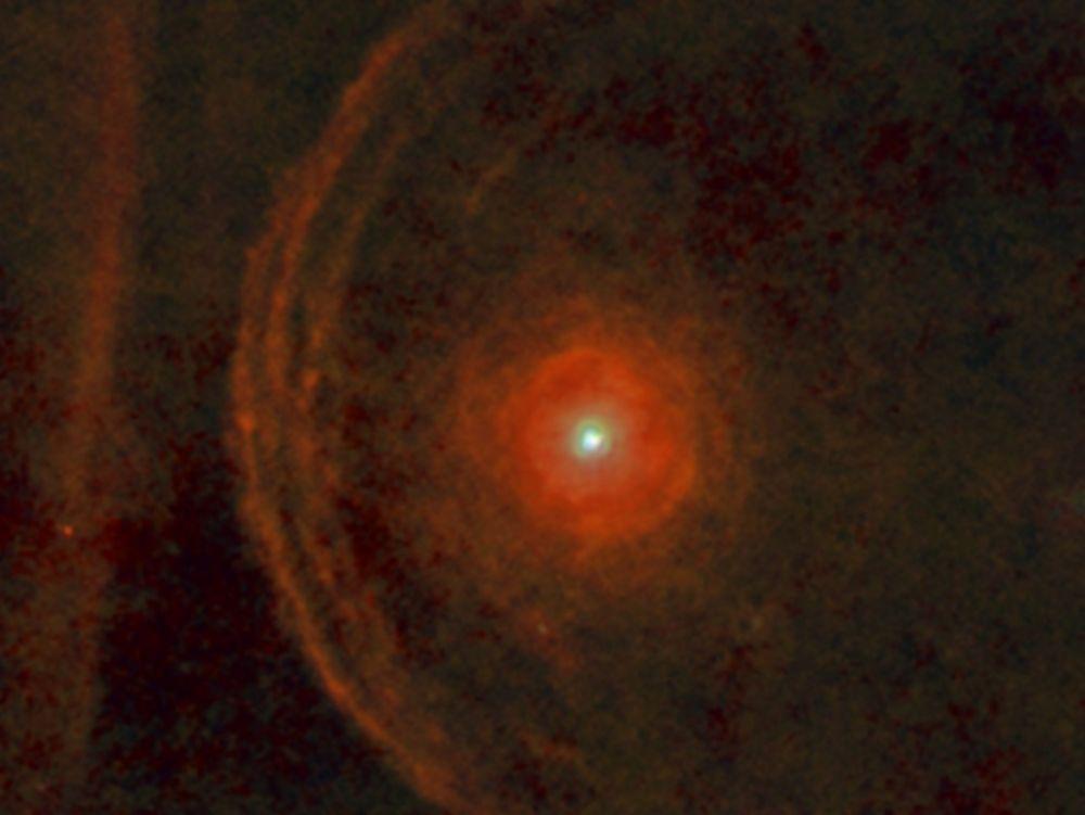 Photo sur fond noir de Bételgeuse représentée par un point brillant, entouré de nimbes rouges qui représentent ses éjections de matière (vent stellaire).