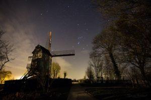 Photo d'un ciel de nuit avec la constellation d'Orion bien visible. Au sol en bas à gauche un moulin, en bas à droite de grands arbres.