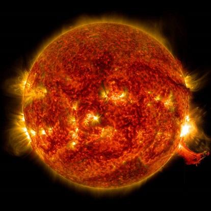 Image sur fond noir du Soleil. On le voit en entier, on distingue une éruption solaire en bas à droite et sur toute la surface rouge orangé du Soleil, des traces d'activité.