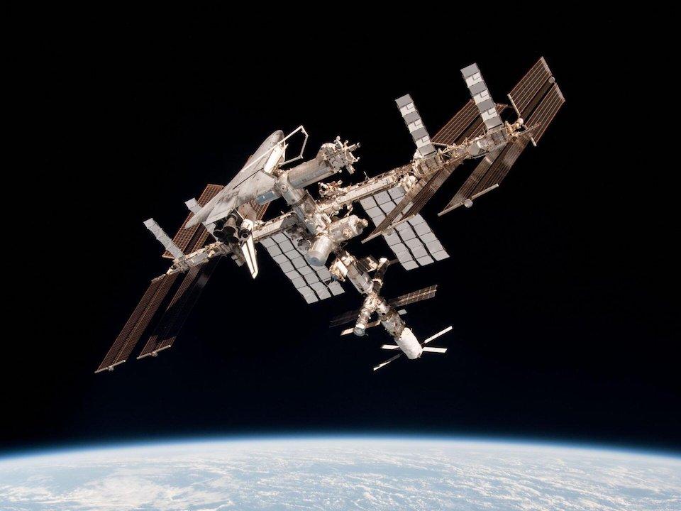 Photo sur fond noir avec la Terre sur la partie basse de l'image, de la Station spatiale internationale en orbite.