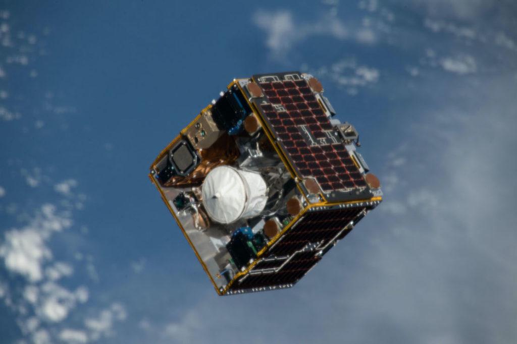 Photo du satellite expérimental RemoveDebris dans l'espace : il est cubique et sur fond bleu (les océans de la Terre)