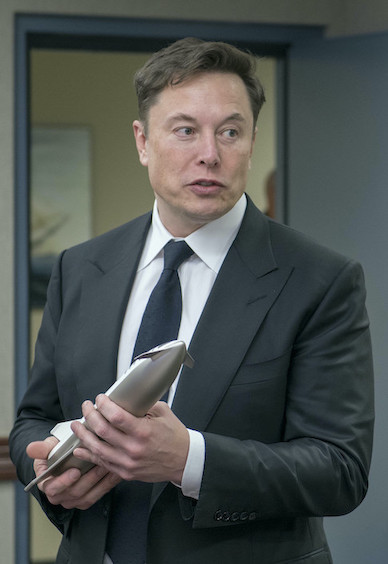 Photo portrait d'Elon Musk, patron de SpaceX, en costume gris foncé avec cravate, une maquette de navette spatiale à la main.