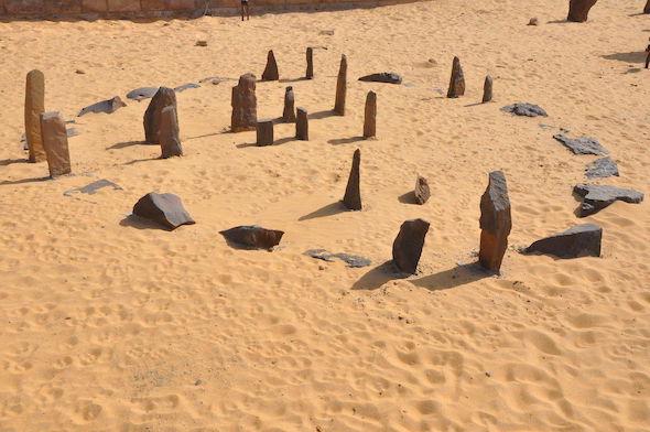 Reconstitution du cercle de pierres de Nabta Playa en Égypte, au musée de la Nubie à Assouan : on y voit sur du sable jaune le cercle de pierres avec notamment les deux couples de pierres alignés avec la position du lever du Soleil au solstice d'été il y a 6000 ans.