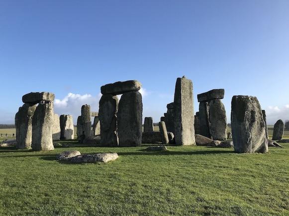 Photo du mégalithe de Stonhenge en Angleterre. On y voit plusieurs gros blocs de pierre gris, plantés dans le sol, au soleil, avec de l'herbe verte sur la partie basse de l'image et du ciel bleu sur la partie haute, les pierres au milieu.