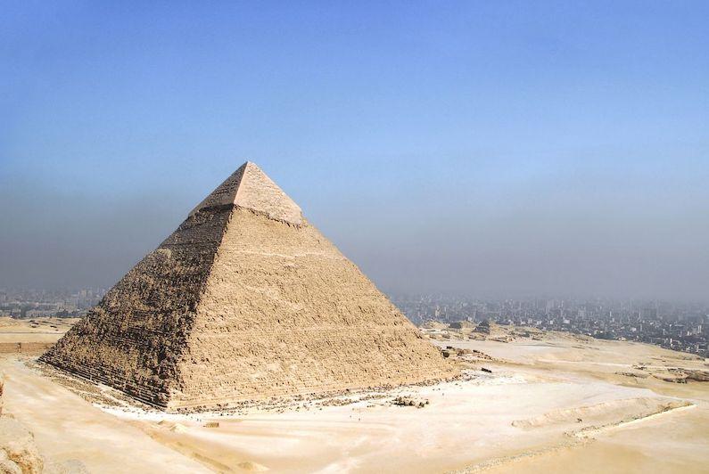 Pyramide de Khéops au soleil, avec la ville du Caire en fond sous un ciel bleu taché d'une nuage de pollution.