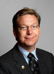 Photo de l'astronome Michael E. Brown : châtain, il porte des lunettes, et est habillé en costume noir, cravate foncée et chemise bleu clair