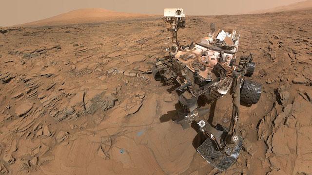Photo autoportrait du rover Curiosity : l'astromobile est sur la droite avec en fond le sol martien et un mont au loin. Le rover possède des éléments blanc et noirs (notamment les roues) et est légèrement recouvert de poussière rouge martienne.