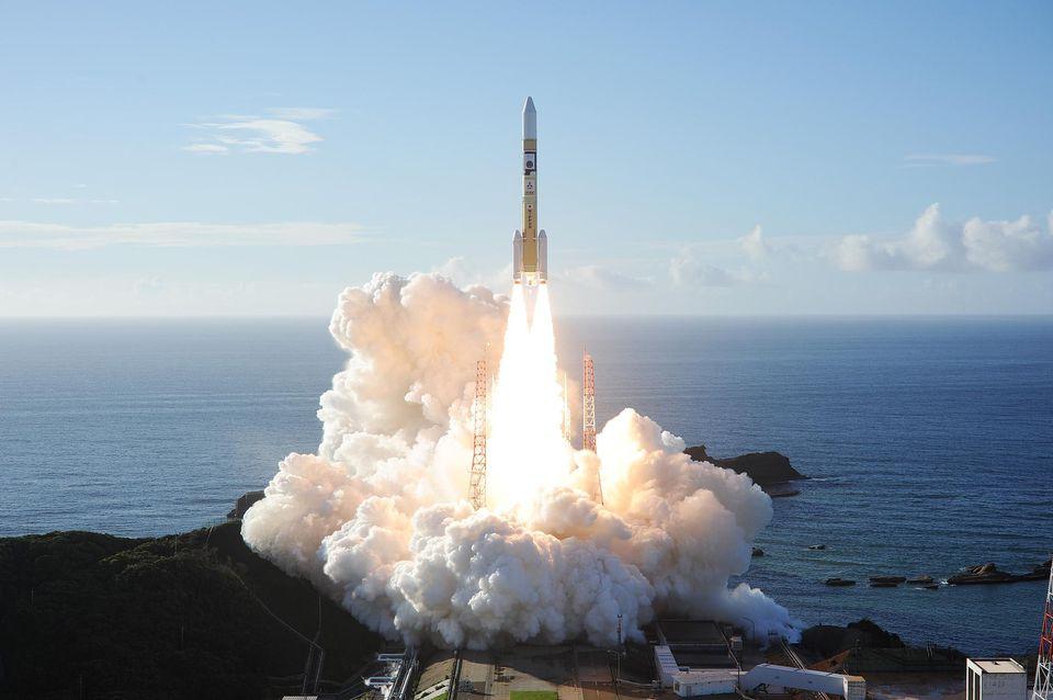 Photo du décollage de la sonde émiratie Al-Amar depuis le Japon : on y voit avec l'Océan en fond, la fusée jaune et blanche au moment du décollage, avec les premières volutes de fumée blanche en arrière plan.