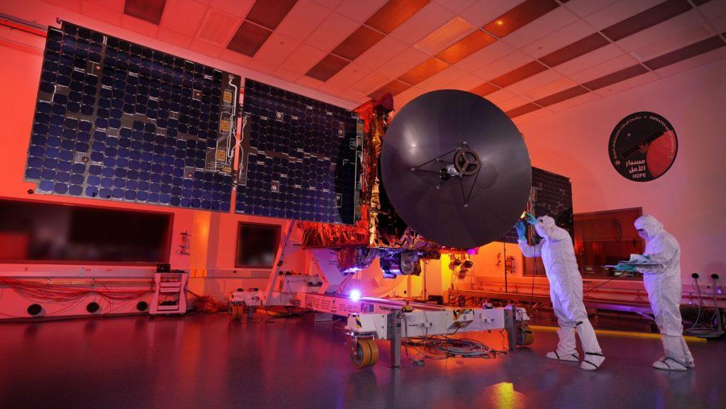 La sonde arabe Hope en salle blanche, on la voit au centre de l'image avec deux ingénieurs à Sto arrivando! droite. Toute la pièce est plongée dans une lumière rouge orangé.