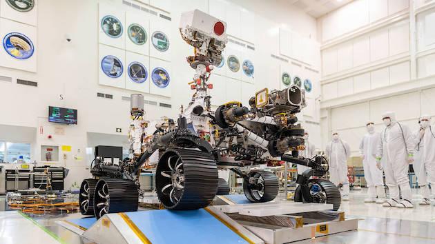 Le rover Perseverance en salle blanche pendant une phase de test : on voit ses six roues sur deux tapis bleu qui simulent le sol accidenté de Mars et sur sa droite se tiennent cinq ingénieurs en combinaison.