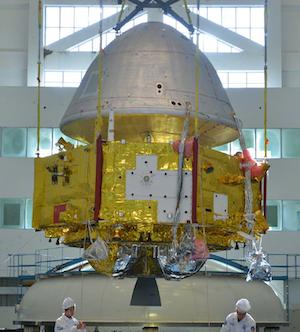 L'orbiteur de Tianwen-1 en cours de test en 2019 : deux ingénieurs sont en bas de l'image, au pied de l'orbiteur constitué d'une partie dorée et d'une coiffe blanche grisée.