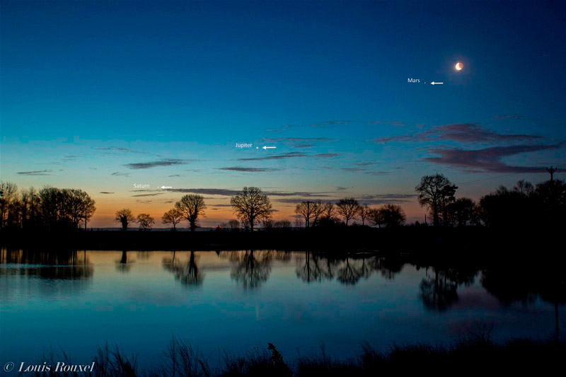 Photo of the Moon, Mars, Jupiter, and Saturn at dawn over a lake. Photo by Louis Rouxel