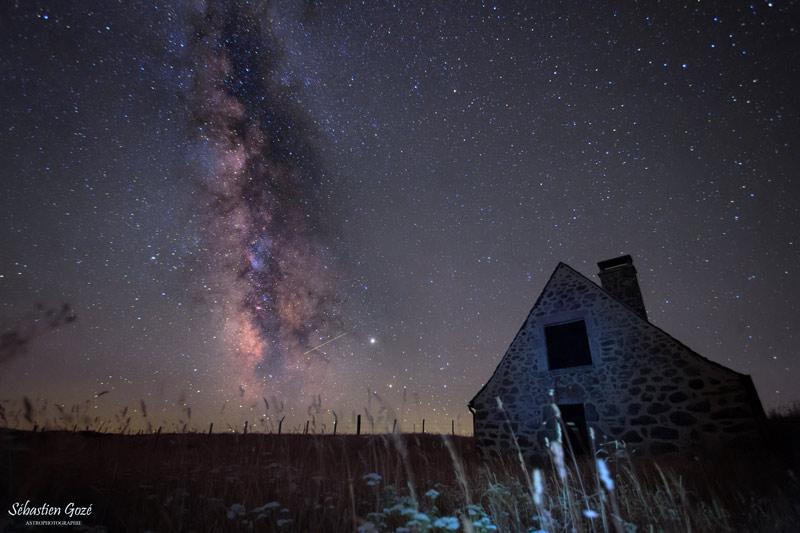 Photo montrant la Voie lactée d'été qui s'élève à la verticale dans le ciel, avec un buron en premier plan (Aveyron).