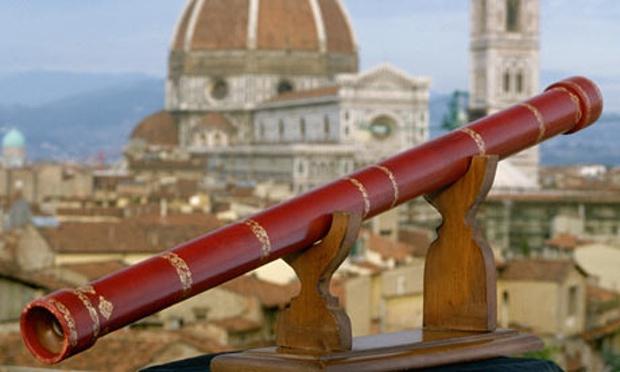 Lunette de Galilée reconstituée, de couleur rouge avec des décorations dorées, elle est représentée en photo avec en fond flou le Duomo de Florence.