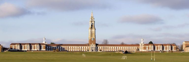Photo de la Royal Hospital School à Greenwich : on voit au premier plan de la pelouse avec terrains de football et rugby, au centre le bâtiment en longueur en pierres beige foncé, fenêtres et volets blancs, avec un clocher au centre. Et en fond le ciel bleu avec des nuages rose et violet.