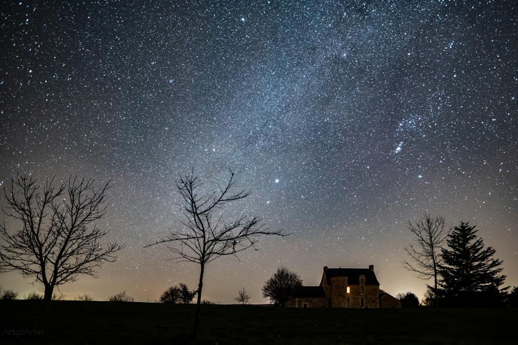 Paysage nocturne avec le ciel étoilé en hiver et la constellation d'Orion et en avant-plan des arbres et une maison.