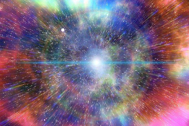Vue d'artiste du Big Bang où l'on voit au centre un point blanc lumineux d'où partent des rayons de couleurs bleu, violet, orange, rouge dans toutes les directions.