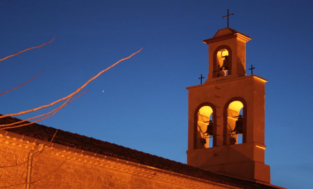 Clocher du sud-ouest sur fond de ciel crépusculaire, avec deux points lumineux qui représentent Saturne et Jupiter.