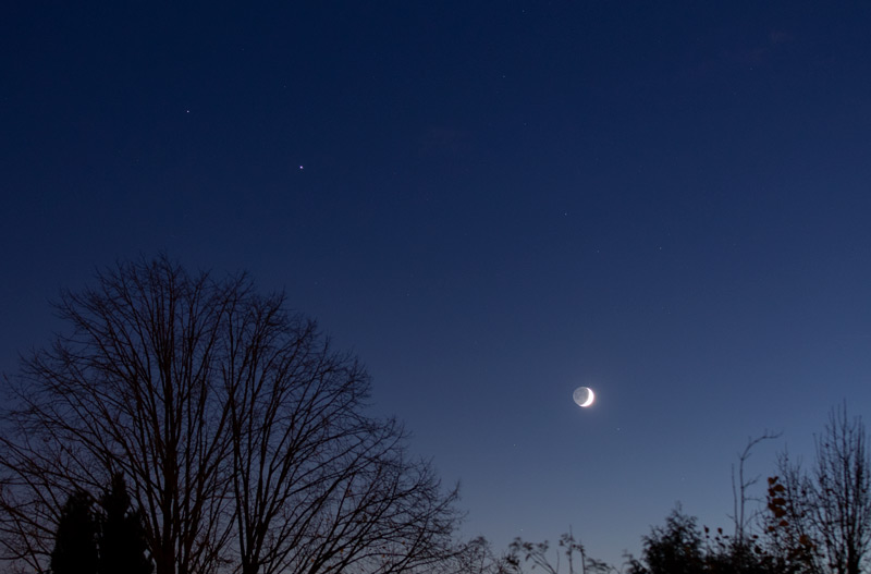 Photo montrant la Lune, Jupiter et Saturne dans le ciel crépusculaire le 18 novembre. La Lune est en croissant avec la lumière cendrée, Jupiter est un point plus brillant que Saturne.