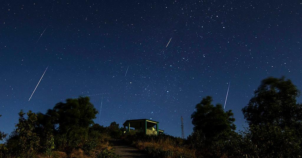 Ciel nocturne avec plusieurs traits blancs qui sont la trace du passage d'étoiles filantes. En premier plan, une colline et une cabane.