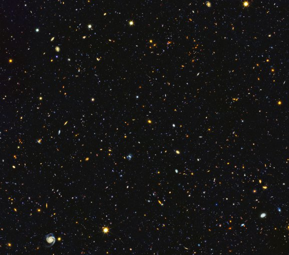 Sur fond noir, une multitudes de points et formes brillants, légèrement bleu, jaune, rouge, orange, vert... Ce sont 15 000 galaxies visibles sur le même cliché. En bas à gauche, on voit nettement une galaxie spirale.