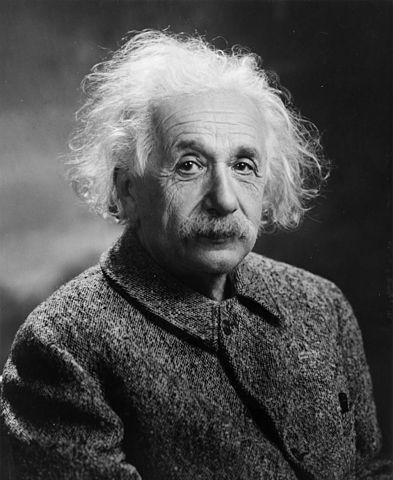 Photo en noir et blanc d'Einstein. On voit son buste et sa tête, il est habillé d'une veste épaisse fermée et a les cheveux blancs, ébouriffés. Il a une moustache.