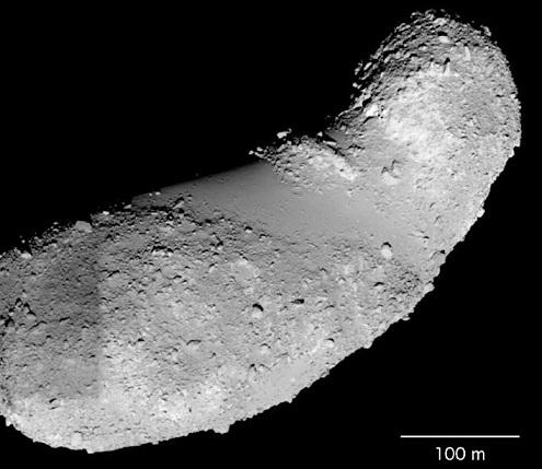 L'astéroïde Itokawa : une patatoïde gris clair, à l'horizontale légèrement inclinée vers la gauche, éclairée par le dessous et parsemée de cailloux. Sur fond noir.