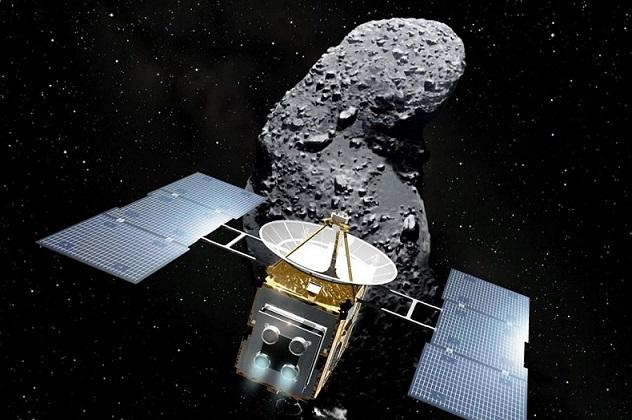 """La sonde Hayabusa 1 est représentée au premier plan, ses panneaux solaires à gauche et à droite, son """"corps"""" carré recouvert de matériau protecteur doré et une parabole sur le dessus. Derrière, on voit l'astéroïde Itokawa, une sorte de patate de couleur grise à la verticale, éclairée par le dessus et parsemée de cailloux. Sur fond étoilé."""