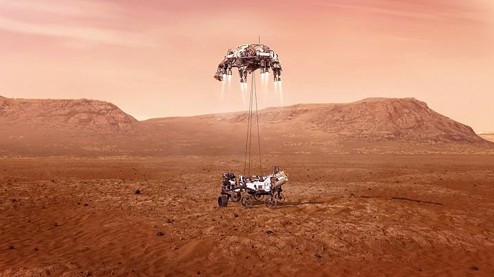 Le sol martien en couleur rouge orangé avec au loin des montagnes. Au milieu de l'image le rover Perseverance qui vient de toucher le sol, il est encore suspendu à l'étage de descente (capsule avec rétrofusées) par des filins.