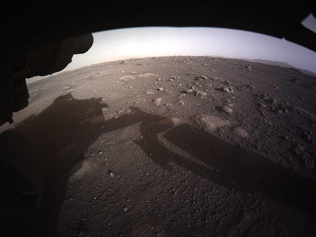 Première image du rover où l'on voit son ombre sur le sol, l'horizon martien sous une forme arrondie par l'effet de caméra. Le sol martien est en couleur marron et parsemé de petites bosses et de divers cailloux.