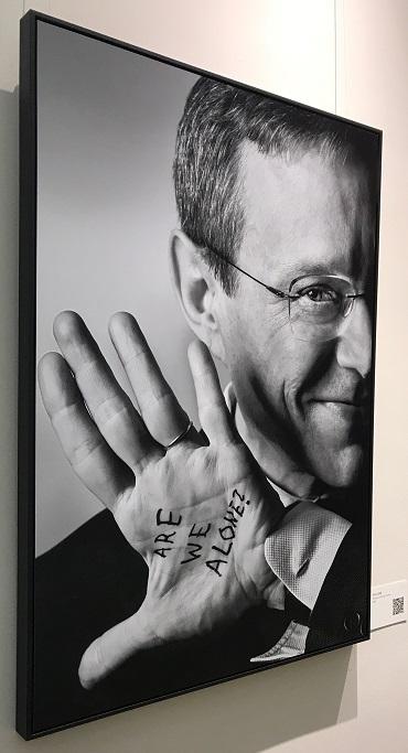 """Photo d'une grande photo en noir et blanc d'Avi Loeb (tableau) dans laquelle il montre la paume de sa main gauche avec écrit le message : """"Are we alone ?"""""""