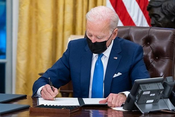 Le président américain Joe Biden à son bureau, en train de signer un document : il a un costume bleu marine, une cravate bleu clair et un masque noir. Derrière lui, on distingue un bout du drapeau américain.