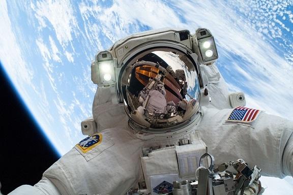 Un astronaute lors d'une sortie extra-véhiculaire : on voit en fond la Terre, et au premier plan sur toute l'image, le scaphandre d'un astronaute dans lequel se reflète l'ISS. Il est habillé d'une imposante combinaison blanche.