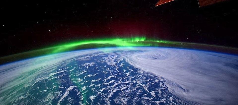 Image satellite d'une aurore boréale au-dessus du Canada : on voit la courbure de la Terre, le bleu de l'océan et des nuages blancs, et au-dessus, des rayons verts qui suivent cette courbure, avec en fond un ciel noir étoilé.