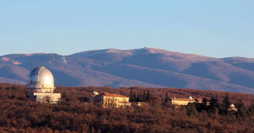 En début de journée, vue sur l'Observatoire de Haute-Provence avec en fond de la moyenne montagne et une végétation de mi-saison, un ciel bleu et au premier plan deux bâtiments de style provençal ainsi qu'à gauche une coupole argentée. Le Soleil éclaire la scène par la droite.