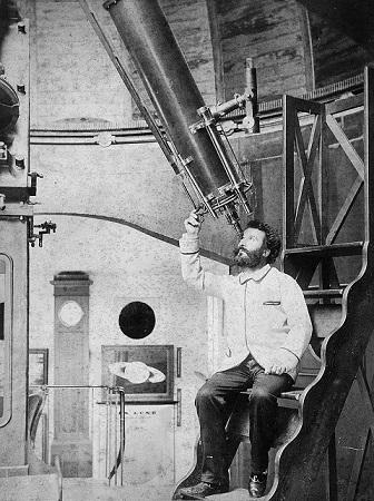 Photo en noir et blanc de Camille Flammarion, assis en blouse blanche en train d'observer dans sa lunette astronomique, pointée au-dessus de lui vers le ciel, au sein de la coupole de son observatoire.